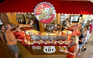 Guests aboard Carnival Breeze carry custom-made hamburgers and fries prepared at GuyÕs Burger Joint, a free burger venue developed in partnership with Food Network personality Guy Fieri. Photo by Andy Newman/Carnival Cruise Lines