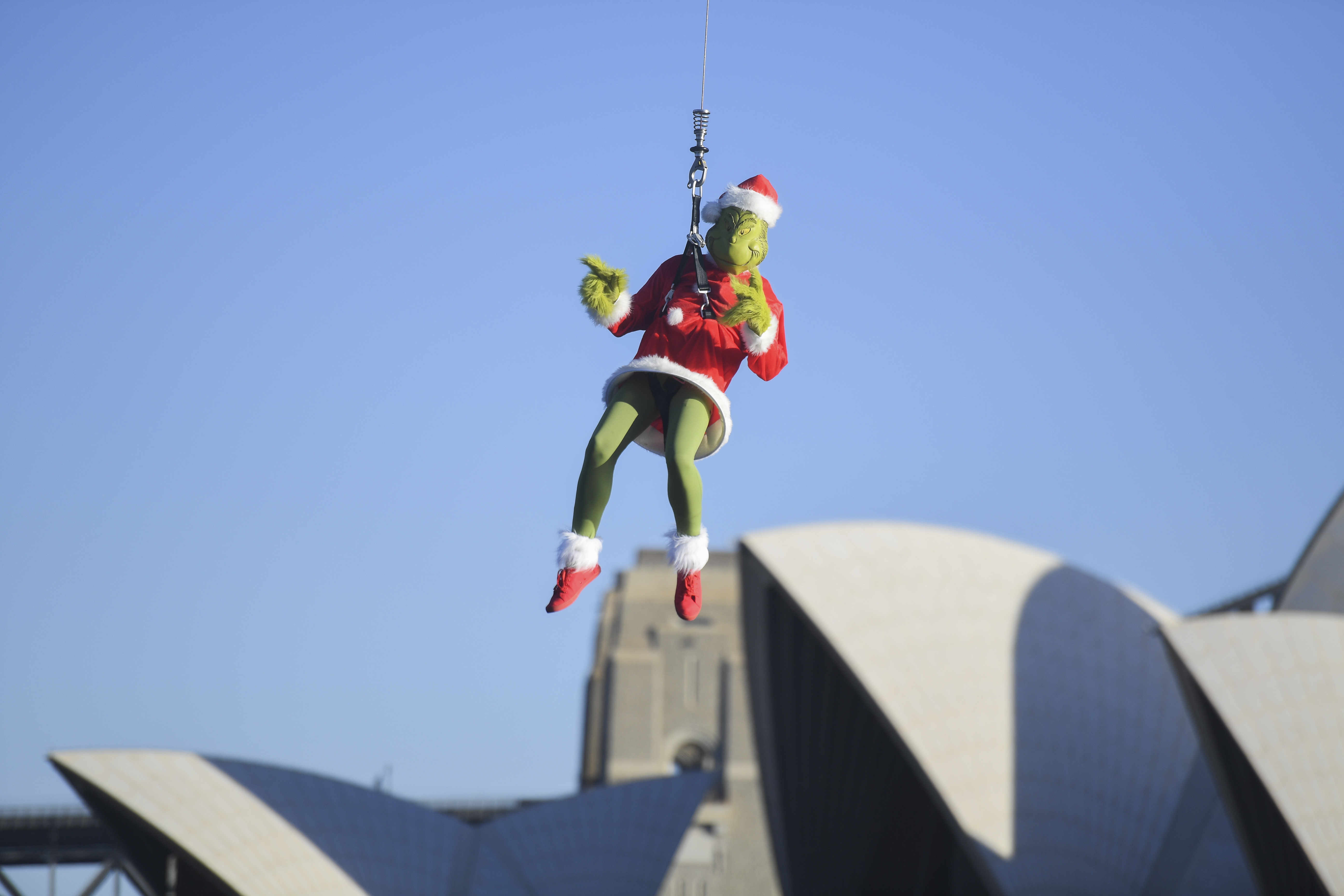 In a Sydney Harbor First, 'The Grinch' Rappels  Down a Rope Via Helicopter to Steal the Fun From Carnival Spirit